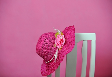 head wear: pink summer hat on chair isolated on pink background. Stock Photo