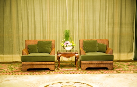 Two antique chairs and table, and bouquet of flowers placed in the middle of them.