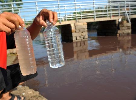 contaminacion del agua: dos botellas en las manos de las personas con agua limpia y sucia. Foto de archivo