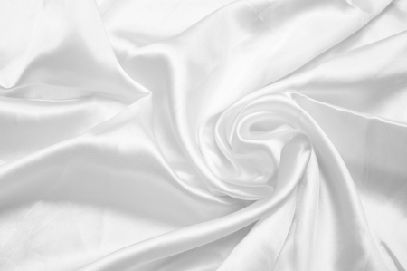 folds: silky smooth white satin background with shine, folds, creases and copyspace.