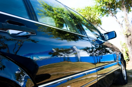 A well polished sedan reflecting beautiful scene,  trees and blue sky.  Stock Photo