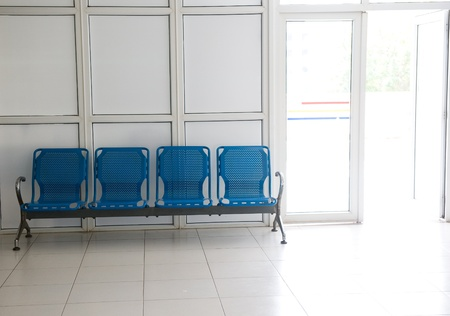 Hospital waiting room with empty blue chairs.