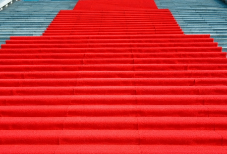 formal party: red carpet on marble stairway welcoming VIPs.