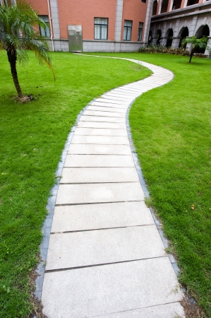 curve stone path in courtyard, and surrounded by green grass.
