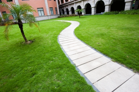 curve stone path in courtyard, and surrounded by green grass.  photo