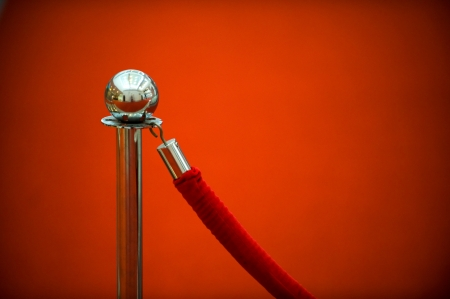 barrier rope: red security rope by red carpet, close-up. Stock Photo