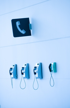 Four public telephones and a telephone sign in one single installation site.  photo