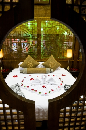 Honeymoon bed topped with rose petals.