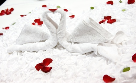Two swans and heart made from towels on honeymoon bed.  photo