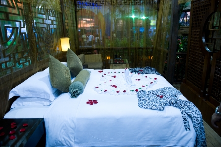 Honeymoon bed topped with rose petals. Stock Photo - 13861083