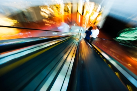 two people in two ways escalator,  because of photo shot by motion blur, the people cant be identify.  photo