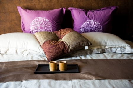 king size bed: cups on a bed in a hotel room. Editorial