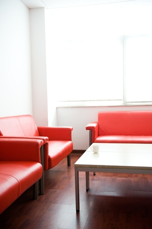 Red leather sofa and white table at waiting room.  photo