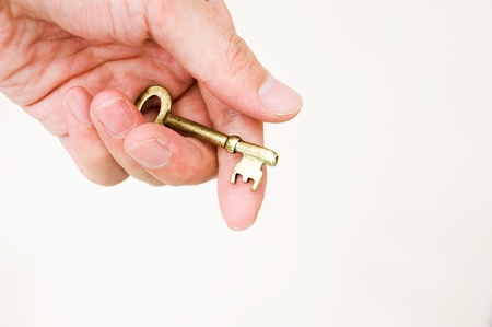 Hand holding a key of success over a white background photo