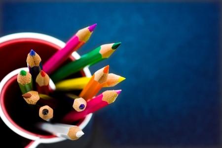 niños en la escuela: Varios lápices de colores sobre fondo azul. Macro con una profundidad muy poca profundidad de campo Foto de archivo