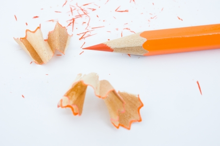 scobs: sharp orange pencil and shavings isolated on white background. Macro with extremely shallow depth of field