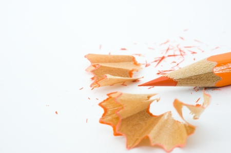sharpenings: sharp orange pencil and shavings isolated on white background. Macro with extremely shallow depth of field
