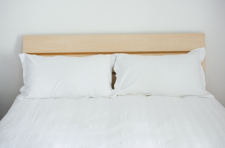 king bed: Group of two white pillows on a bed with headboard.