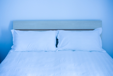 Group of two white pillows on a bed with headboard. photo