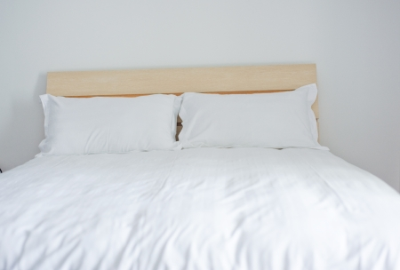 bed sheet: Group of two white pillows on a bed with headboard.
