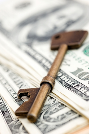 Golden key on top of US dollar bills. Stock Photo - 13864176