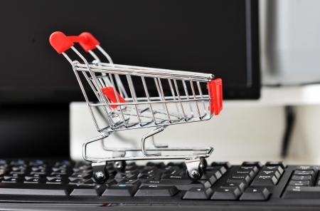empty shopping cart on the keyboard of computer, on-line shopping concept. photo
