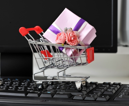 Shopping cart with gift boxe on the keyboard of computer. photo