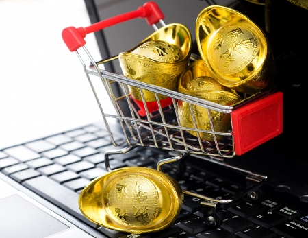 shopping cart full of Chinese gold ingot ornaments on the laptop, on-line shopping concept.