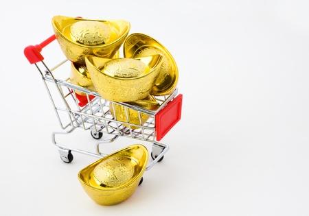 shopping cart full of Chinese gold ingot ornaments isolated on white.  photo