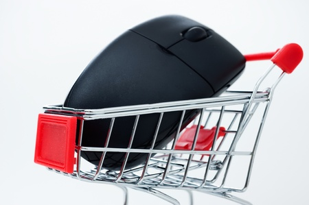 Computer mouse in a miniature-shopping cart. Stock Photo - 13863634