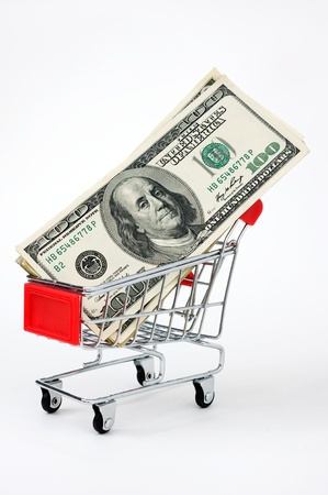 Shopping cart and stocks of dollars close up shot. photo
