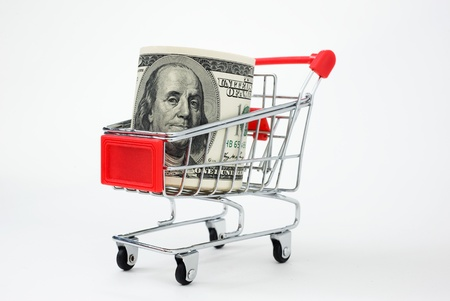 Shopping cart and stocks of dollars close up shot. photo