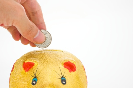 golden piggy bank and hand with coin isolated on white background  photo
