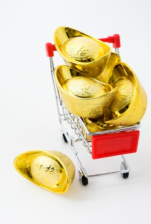 shopping cart full of Chinese gold ingot ornaments isolated on white.   The characters on gold ingot means  Making plenty of money    photo