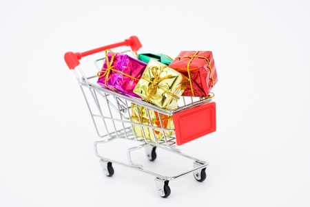 Many colors of christmas gifts in a shopping cart isolated on white background. photo