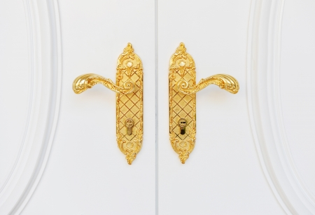 Close up of double antique gold plated door handle on the white door.   photo