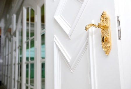 Close up of antique gold plated door handle on the white door.  photo