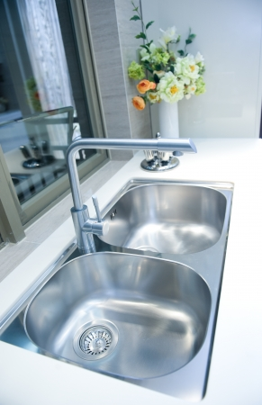 faucets: Interior of a modern kitchen with stanless steel double sink.