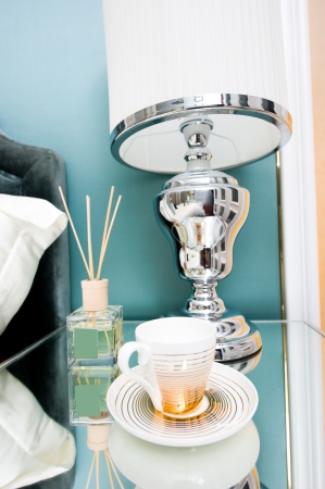 Detail of bed and bedside table with lamp and cup in a hotel room.   photo