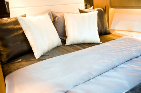 bedlinen: Hotel room bed with many pillows.