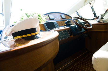 Rudder, compass and captains hat on yacht  photo