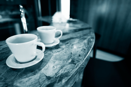 countertop: two cup of drink on the counter at a diner, blue tone.