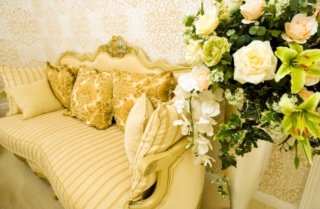 Modern sofa with cushions and flowers in front of beautiful wallpaper.  photo