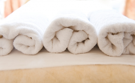 terry: Closeup of soft white towels, rolled and piled.