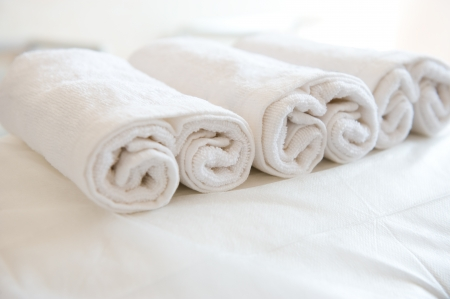 wash cloth: Closeup of soft white towels, rolled and piled.