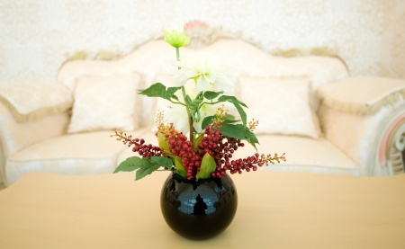 vase of flowers in a hotel room on coffee table. photo