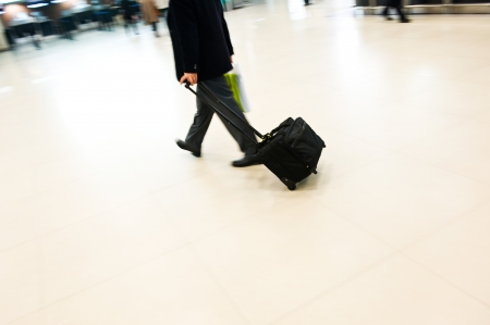 Businessman pulling a trolley luggage at station.  photo