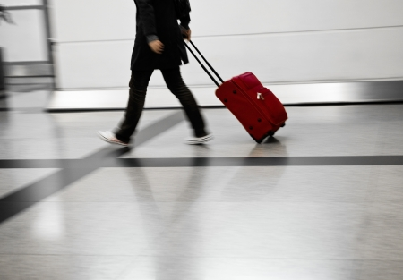 Man with red bags rushing at the airport photo