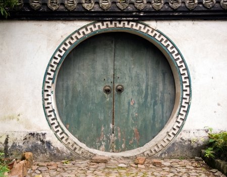 old green wood gates with two knockers, China. photo