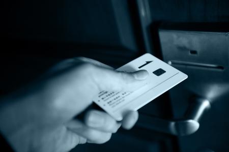 toegangscontrole: Een hand plaatst sleutelkaartsysteem in de elektronische vergrendeling, blauwe tint.